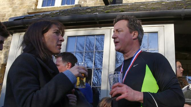 British Prime Minister David Cameron enjoys a beer after competing in the Great Brook Run, a mile long course through water and mud, at Chadlington in southern England