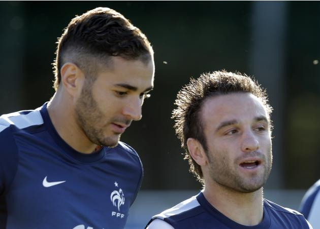 France's national soccer team players Benzema and Valbuena warm up during a training session in Clairefontaine