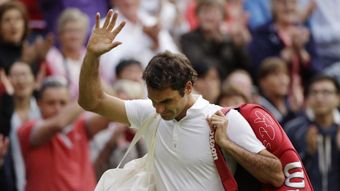 Roger Federer of Switzerland waves to the crowd as he walks off the court after his defeat to Sergiy Stakhovsky of Ukraine in their Men's second round singles match at the All England Lawn Tennis Championships in Wimbledon, London, Wednesday, June 26, 2013. (AP Photo/Anja Niedringhaus)
