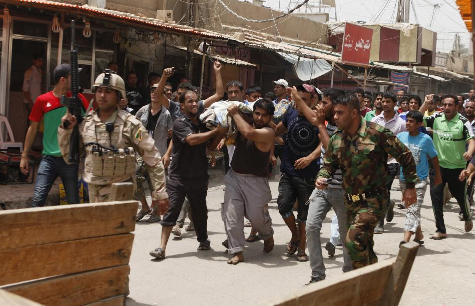 People carry the body of a victim of a car bomb attack in the Washash neighborhood of Baghdad, Iraq, Thursday, June 28, 2012. Police say a series of bombs around Iraq's capital have killed and wounded scores of people. (AP Photo/Karim Kadim)