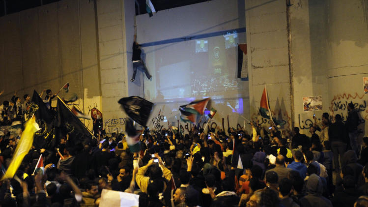 Palestinians gather next to a section of Israeli separation barrier at the entrance to the west bank city of Bethlehem to watch a large screen showing the U.N. General Assembly votes on a resolution to upgrade the status of the Palestinian Authority to a nonmember observer state, Thursday, Nov. 29, 2012.  The U.N. General Assembly has voted by a more than two-thirds majority to recognize the state of Palestine. The resolution upgrading the Palestinians' status to a nonmember observer state at the United Nations was approved by the 193-member world body late Thursday by a vote of 138-9 with 41 abstentions. (AP Photo/Nasser Shiyoukhi)