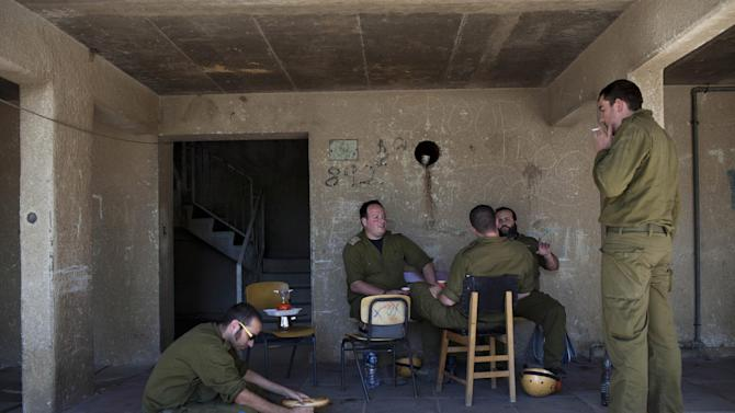 Israeli soldiers of the Home Front Command rescue unit have their lunch during a search and rescue drill at a site simulating a collapsed school, in the northern Israeli city of Nazareth Illit, Monday, May 27, 2013. Israel is holding a national emergency response drill on Monday simulating a large scale missile attack which the army said will this year focus on the threat of unconventional weapons at a time of growing regional tensions. (AP Photo/Oded Balilty)