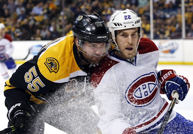 Boston Bruins defenseman Johnny Boychuk (55) checks Montreal Canadiens right wing Dale Weise (22) during the first period in Game 1 of an NHL hockey s...