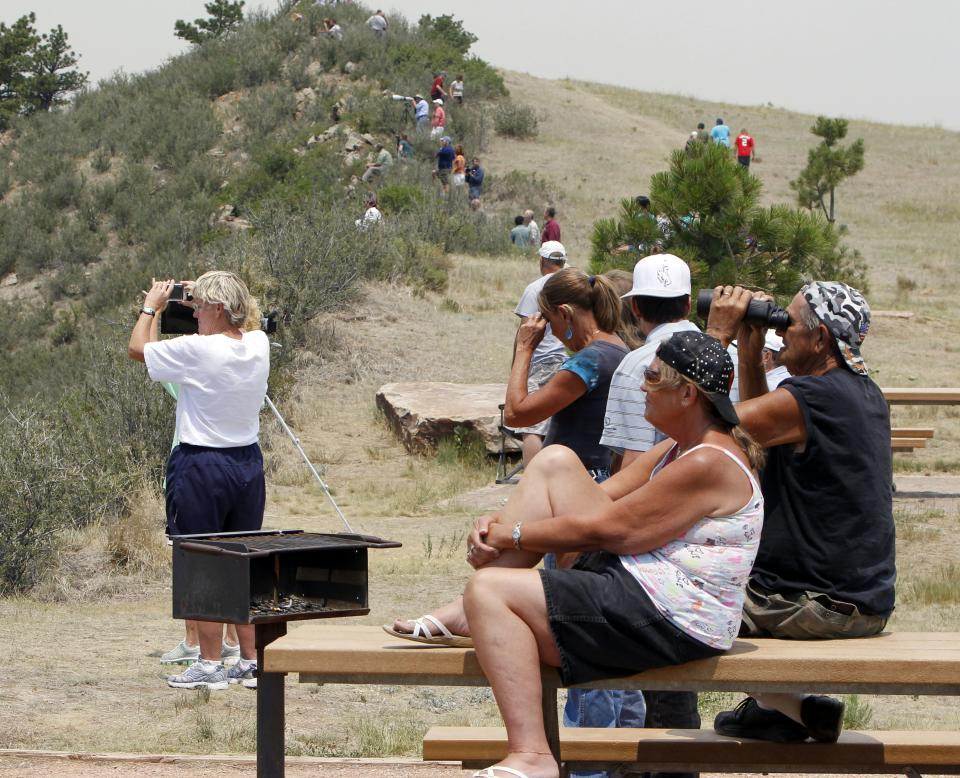 People watch from a hill as the High Park wildfire burns near Fort Collins, Colo., on Monday, June 11, 2012. The wildfire is burning out of control in northern Colorado, while an unchecked blaze choked a small community in southern New Mexico as authorities in both regions battled fires Monday. (AP Photo/Ed Andrieski)
