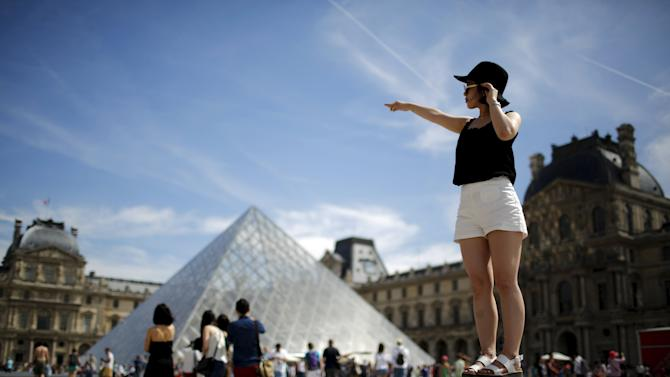 Tourist poses for a souvenir picture near the Pyramid of the Louvre Museum in Paris