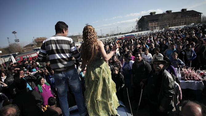"""This Saturday, March 23, 2013  photo shows people watching Roma girl and boy from the Kalaidzhi community dancing on the trunk of a car, during so called """"Roma bridal market"""". The Kalaidzhi, who represent only a small portion of the estimated 700,000 Roma in Bulgaria, are almost all devout Orthodox Christians who keep teenage boys and girls separate. Parents sometimes remove girls from school at 15 or even earlier to keep them from mixing with boys. The isolation is broken only by Internet chats and the twice-a-year bridal fairs.  (AP Photo/Valentina Petrova)"""