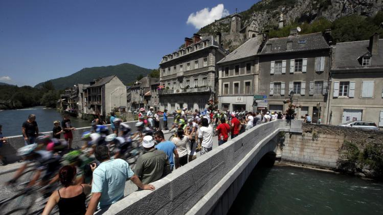 The pack of riders cross a bridge at Saint Beat during the 17th stage of the Tour de France cycle race
