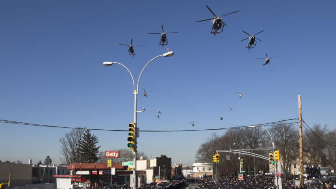 Police helicopters fly over officers along the funeral procession route during the funeral service of New York City police officer Rafael Ramos in the Glendale section of Queens, Saturday, Dec. 27, 2014, in New York. Ramos and his partner, officer Wenjian Liu, were killed Dec. 20 as they sat in their patrol car on a Brooklyn street. The shooter, Ismaaiyl Brinsley, later killed himself. (AP Photo/John Minchillo)