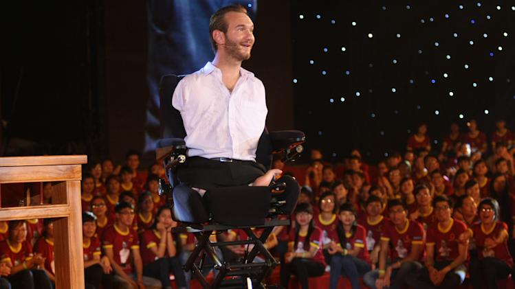 In this Thursday, May 23, 2013 photo, Nick Vujicic, an Australian evangelist who  was born with no limbs, on his wheelchair, delivers his speech to a crowd of about 25,000 students and young people at My Dinh national stadium in Hanoi, Vietnam.  Vujicic, who is able to stand up and move around on his pelvis, shuffled round on a small table set up on a stage on corner of the field. In a talk laced with jokes, platitudes and attempts at Vietnamese, he spoke out against bullying and drinking; on the need for forgiveness and hope; and respect for family. All those themes resonate with Vietnamese and their leaders, one of whom _ the vice president _ was watching from the VIP area. (AP Photo/Na Son Nguyen)