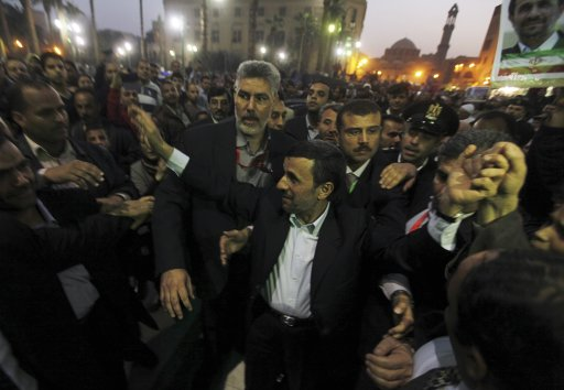 Iran's President Mahmoud Ahmadinejad waves to people as he arrives in front of the Al-Hussein mosque in old Cairo