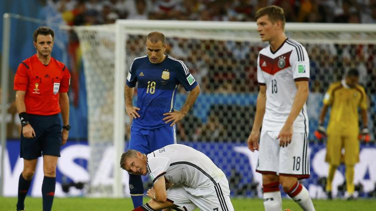 Germany's Schweinsteiger stretches beside teammate Kroos and Argentina's Palacio during extra time in their 2014 World Cup final at the Maracana stadium in Rio de Janeiro