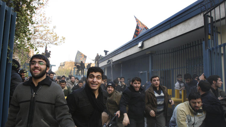 Iranian protesters enter the British Embassy, in Tehran, Iran, Tuesday, Nov. 29, 2011. Dozens of hard-line Iranian students stormed the British Embassy in Tehran on Tuesday, bringing down the Union Jack flag and throwing documents from windows in scenes reminiscent of the anger against Western powers after the 1979 Islamic Revolution. The mob moved into the diplomatic compound two days after Iran's parliament approved a bill that reduces diplomatic relations with Britain following London's support of recently upgraded Western sanctions on Tehran over its disputed nuclear program. (AP Photo/Vahid Salemi)