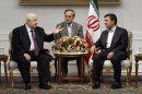 Syrian Foreign Minister Walid al-Moallem, left, talks with Iranian President Mahmoud Ahmadinejad, during their meeting at the Iranian presidency office in Tehran, Iran, Sunday, July 29, 2012. An unidentified interpreter sits at center. (AP Photo/Vahid Salemi)