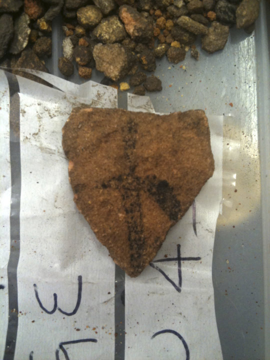 In this May 2012 photo provided by Bryce Barker, a fragment of Aboriginal rock art on granite found in Australian Outback is seen on a plastic bag. University of Southern Queensland archaeologist Bryc