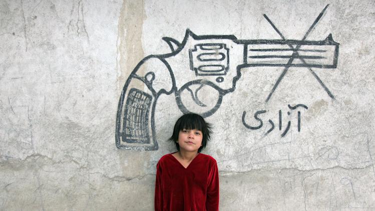 "An Afghan child poses for a photograph beneath graffiti of a pistol, with writing that reads, ""freedom,"" in Kabul, Afghanistan, Sunday, Feb. 10, 2013. (AP Photo/Ahmad Nazar)"