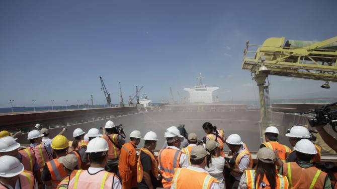 Visitors observe as raw sugar is loaded into a cargo ship in Acajutla