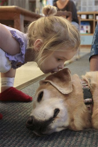 Sunnie Horkstra, 2, a patient at Sutter Memorial Hospital kisses Hazel, a pediatric therapy dog, on her last day on the job at the hospital's children's center in Sacramento, Calif., Wednesday, June 2