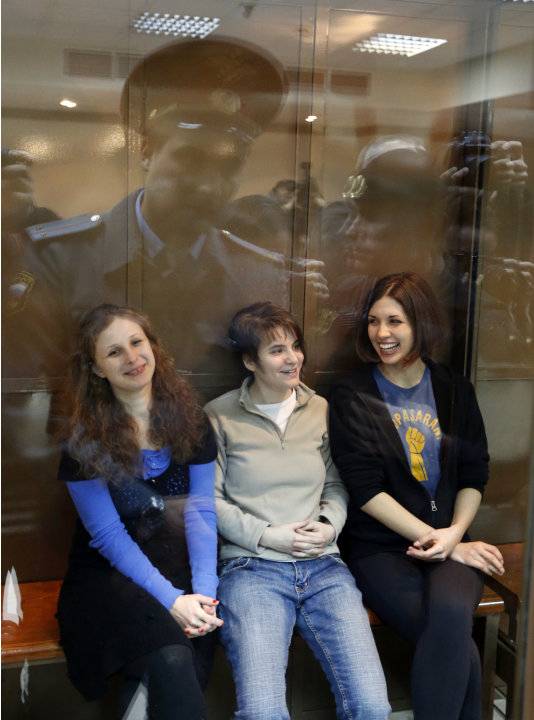 FILE - In this Monday Oct. 1, 2012 file photo, feminist punk group Pussy Riot members, from left, Maria Alekhina, Yekaterina Samutsevich and Nadezhda Tolokonnikova sit in a glass cage at a court room