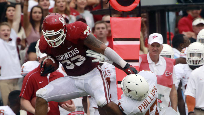 FILE - This oct. 13, 2012 file photo shows Oklahoma fullback Trey Millard (33) breaking a tackle against Texas cornerback Adrian Phillips (17) and defensive back Mykkele Thompson (2) during the first half of an NCAA college football game at the Cotton Bowl in Dallas. Millard continues to take on a bigger role for No. 8 Oklahoma, going from being a blocker to a threat as a runner and pass-catcher. His task this week: to try and neutralize standout Notre Dame linebacker Manti Te'o.  (AP Photo/Michael Mulvey, File)
