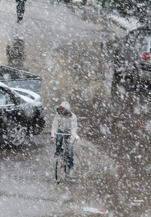 A Syrian man rides his bicycle in during snow fall in Damascus on January 9, 2013 as a fierce storm whipped the region this week and temperatures dropped dramatically.   AFP PHOTO/ STR