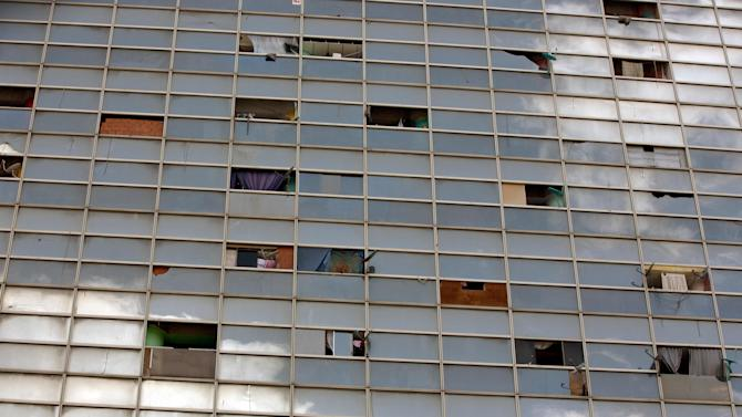 Broken windows are seen covered with wood planks at the the world's tallest slum, a half-built skyscraper that was abandoned in the 1990s and was transformed by squatters into a vertical ghetto, in Caracas, Venezuela, Tuesday, July 22, 2014. Tuesday saw the beginning of the end for one of Caracas' strangest landmarks. Officials and armed soldiers began moving out the first of thousands of squatters who have lived for nearly a decade in a soaring, half-built skyscraper in the heart of Caracas. (AP Photo/Fernando Llano)
