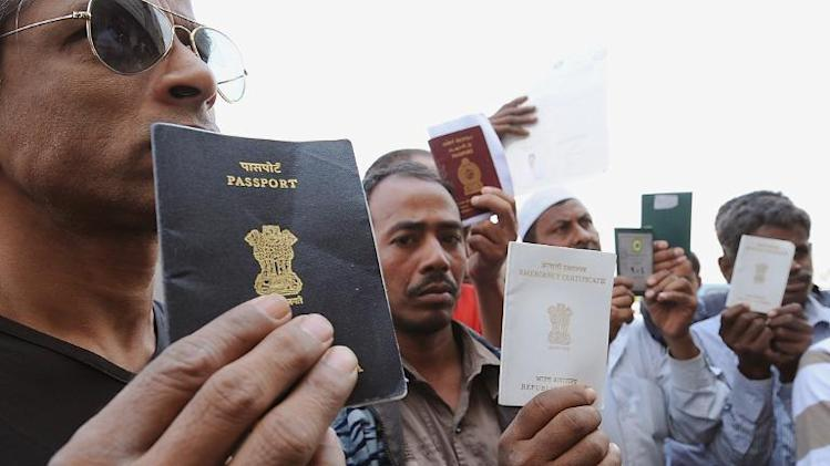 Foreign workers show their passports as they gather outside a Saudi immigration office waiting for an exit permit as Saudi security begin their search campaign against illegal laborers, on November 4, 2013 in downtown of Riyadh