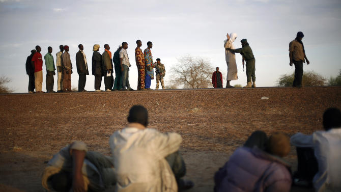 FILE - This Feb. 12, 2013 file photo shows travelers driving from Niamey, Niger, lining up to be searched at the entrance of Gao, northern Mali. Al-Qaida's North African arm is trying something new to stay relevant: Twitter. Al-Qaida in the Islamic Maghreb, or AQIM, is trying to move the battleground elsewhere, seeking to tap into social grievances and champion mainstream causes such as unemployment, all in bid to reverse decline and win new followers, appealing to widespread concerns, such as the repression and a sense of injustice that galvanized the Arab Spring revolts. (AP Photo/Jerome Delay, File)