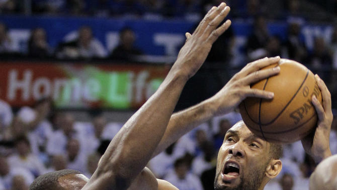 San Antonio Spurs center Tim Duncan, right, looks for a shot as Oklahoma City Thunder center Kendrick Perkins defends during the first half of Game 4 in the NBA basketball playoffs Western Conference finals, Saturday, June 2, 2012, in Oklahoma City. (AP Photo/Eric Gay)