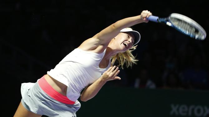 Maria Sharapova of Russia serves against Caroline Wozniacki of Denmark during their WTA Finals singles tennis match at the Singapore Indoor Stadium
