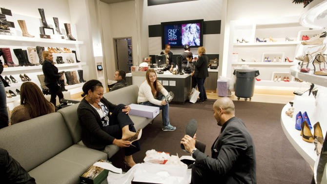 In this photo of Friday, Oct. 12, 2012, customers shop at Macy's shoe department in New York. Shoes are coming out of the closet and landing under the Christmas tree. They're a top seller this holiday season _ a big feat considering they don't usually make peoples' gift lists. (AP Photo/Mark Lennihan)