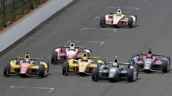 Tony Kanaan, second from right, of Brazil, passes Ryan Hunter-Reay (1) on the 197th lap to takes the lead on his way to winning the Indianapolis 500 auto race at the Indianapolis Motor Speedway in Indianapolis, Sunday, May 26, 2013. Carlos Munoz, of Colombia, (26) finished second, Ray finished third, and Marco Andretti (25) finished fourth. (AP Photo/AJ Mast)