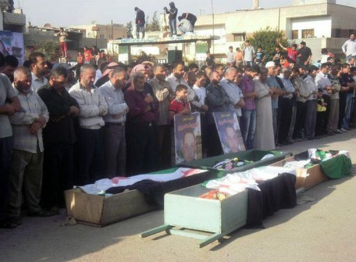 Syrians hold a funeral procession for people who were allegedly killed during unrest in the city of Daraa