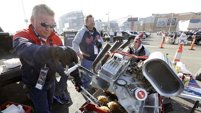New England Patriots fan Billy Burrows, left, from Billerica, Mass., cooks burgers on a custom grill created from a 350 Chevrolet short block engine while tailgating with friends in the parking lot before an NFL football game between the Patriots and the Detroit Lions Sunday, Nov. 23, 2014, in Foxborough, Mass