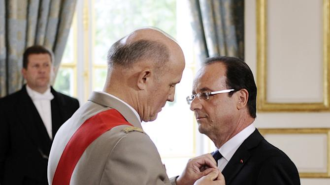 """Francois Hollande is awarded """"Grand Maitre"""" in the Order of the Legion of Honor, from chancellor of France's National Order of the Legion of Honor, General Jean-Louis Georgelin, as he is officially named as France's president at the Elysee presidential Palace in Paris, Tuesday, May 15, 2012. (AP Photo/Fred Dufour, Pool)"""