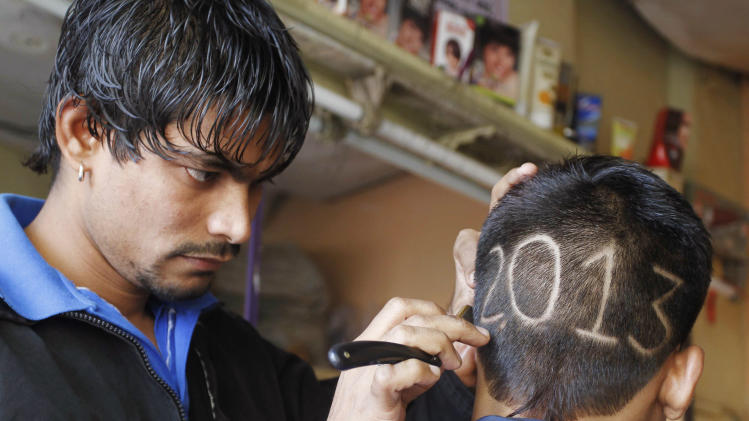 An Indian barber gives finishing touches to the hair style of a young boy with numbers to welcome the New Year 2013 in Ahmadabad, India, Monday, Dec. 31, 2012.  (AP Photo/Ajit Solanki)