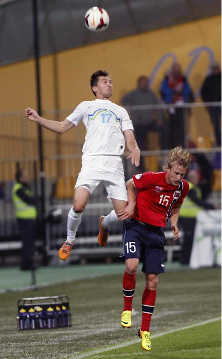 Slovenia's Andraz Kirm, left, jumps for a ball with Norway's Per Ciljan Skjelbred during the 2014 World Cup group E qualifier soccer match between Slovenia and Norway in Maribor, Slovenia, Friday, Oct