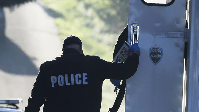 "Police officers carry a shotgun, a dictionary, and a copy of the Reader's Digest book ""Fight Back and Win: What to Do When You Feel Cheated or Wronged"" as they collect evidence from the scene of an overnight shooting that left five people dead, including a suspect who was shot by arriving officers, police said early Monday, April 22, 2013, at an apartment complex in Federal Way, Wash. Federal Way Police Cmdr. Kyle Sumpter confirmed Monday that the shotgun pictured was used by the suspect in the shooting.(AP Photo/Ted S. Warren)"