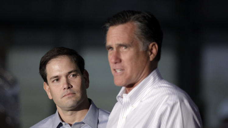 Sen. Marco Rubio, R-Fla. listens at left as Republican presidential candidate, former Massachusetts Gov. Mitt Romney speaks during a news conference prior to a town hall-style meeting in Aston, Pa., Monday, April 23, 2012. (AP Photo/Jae C. Hong)