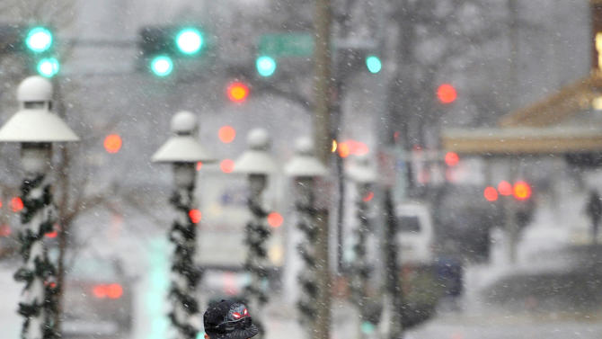 Chelsea Henning shields herself from pelting snow while walking to work with Josh Summers, both of Lincoln, Neb., Wednesday, Dec. 19, 2012, at 13th and P Streets in Lincoln, Neb. A blizzard warning is in effect until noon on Thursday. (AP Photo/The Journal-Star, Matt Ryerson) LOCAL TV OUT; KOLN-TV OUT; KGIN-TV OUT; KLKN-TV OUT