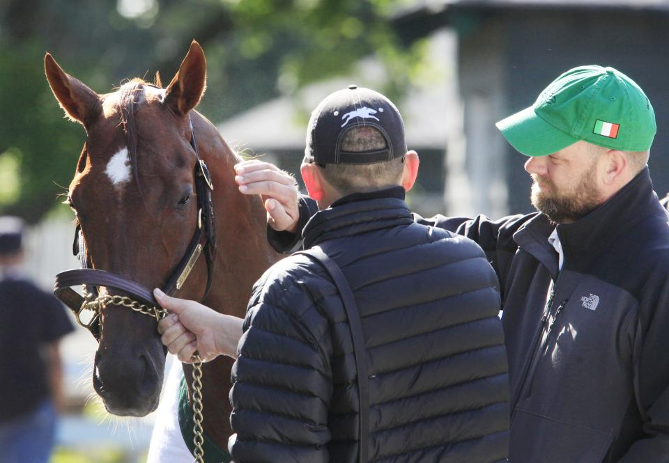 Trainer Doug O'Neill, right, gives I'll Have Another a pat on the neck after a morning workout at Belmont Park in Elmont, N.Y., Tuesday, June 5, 2012. I'll Have Another is trying to win the Triple Crown in Saturday's Belmont Stakes. (AP Photo/Mark Lennihan)