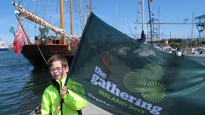 This May 17, 2013 photo shows 5-year-old Callum MacCobb posing with his flag on Dublin docks as he greeted the tall ships sailing into the port. The ships were replicas of vessels that once carried millions of emigrants away from Ireland to seek their fortune elsewhere. The event was part of The Gathering, a yearlong tourism initiative to boost Ireland's economy by luring its diaspora home. (AP Photo/Helen O'Neill)