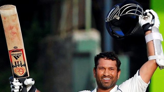 Tendulkar raises his bat and helmet after scoring his century against Sri Lanka during the third day of their second test cricket match in Colombo