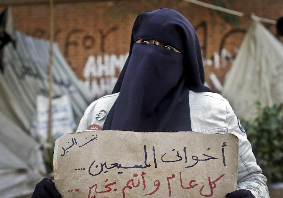 "An Egyptian woman holds a poster with Arabic that reads, ""my Christian siblings.. happy new year.."" in front of the presidential palace in Cairo, Egypt, Monday, Dec. 31, 2012. (AP Photo/Amr Nabil)"