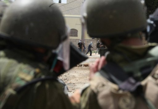 Palestinian protesters throw stones toward Israeli soldiers in the West Bank in April 2012. An Israeli soldier who has refused to serve in the Palestinian territories has gone on hunger strike in a military prison in solidarity with Palestinian administrative detainees, a report said