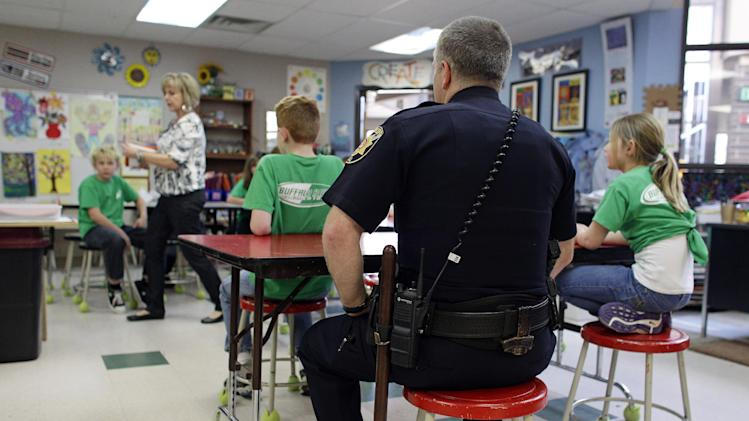 FILE - In this Thursday, Jan. 31, 2013 file photo, Douglas County Sheriff's Lt. Brian Murphy sits in on part of an art class while spending some time at Buffalo Ridge Elementary School, part of a new cooperative effort between law enforcement and schools for more routine police presence at local primary schools, in Castle Pines, Colo. Since the December school attack in Connecticut, county police have begun a practice of completing their paperwork from their cruisers in elementary school parking lots, and are encouraged to spend more time inside schools. (AP Photo/Brennan Linsley, File)