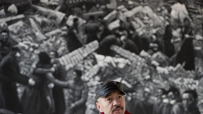 In this photo taken on Tuesday, Dec. 25, 2012, Beijing-based artist Liu Yi pauses in front of his painting of Tibetans at his studio in Songzhuang art village in Tongzhou, on the outskirt of Beijing. Liu is working on a series of black-and-white portraits he knows will never be shown in a Chinese gallery. His varied subjects - men and women, young and old, smiling and pensive - have one thing in common: They are Tibetans who have set themselves on fire to protest repressive Chinese rule. (AP Photo/Andy Wong)