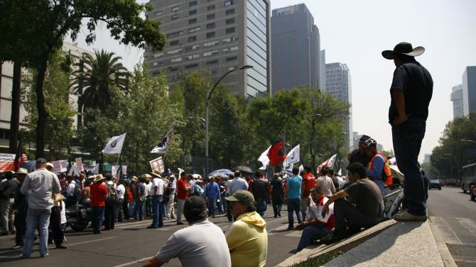 """Demonstrators protest outside the U.S. embassy before the arrival of President Barack Obama in Mexico City, Thursday, May 2, 2013. The protesters are from an organization that represents people who used to be part of a workers program between Mexico and the U.S. called """"Braceros,"""" members of the Mexican Union of Electricians (SME) and pro-migrant groups.  (AP Photo/Marco Ugarte)"""