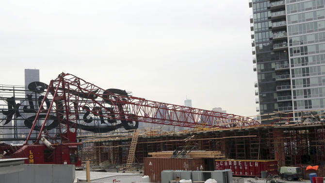 "FILE- In this Jan. 9, 2013 file photo, a mangled crane lies at the construction site in the Queens borough of New York where it collapsed behind a big neon ""Pepsi Cola"" sign, a local landmark. On Wednesday, Jan. 30, 2013, the New York City Buildings Department cited Paul Greer, the crane operator, and the contractor, Cross Country Construction LLC with safety violations that could cost each of them $64 thousand in fines. (AP Photo/Mary Altaffer, File)"