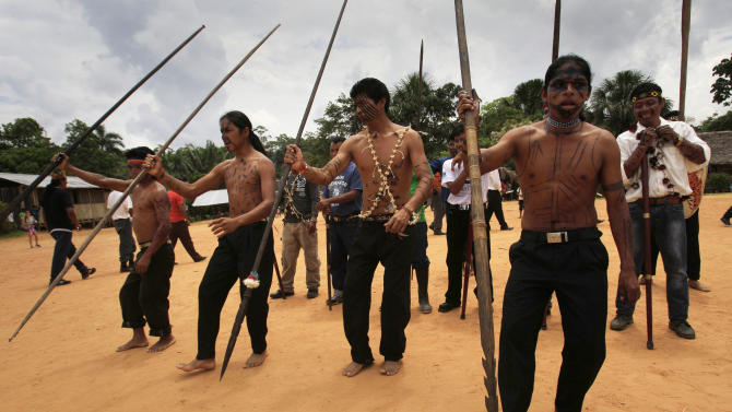 FILE - In this Aug. 12, 2012 file photo, Sarayaku Indian men dance during celebrations in Sarayaku village in Ecuador. Ecuador's President Rafael Correa threatened unspecified consequences Tuesday, April 29, 2014 for the fiercely independent indigenous community in Ecuador's Amazon that is harboring three political opponents who face prison for defaming him. The remote community is famed among the indigenous in the Americas for successfully resisting oil drilling. (AP Photo/Dolores Ochoa, File)