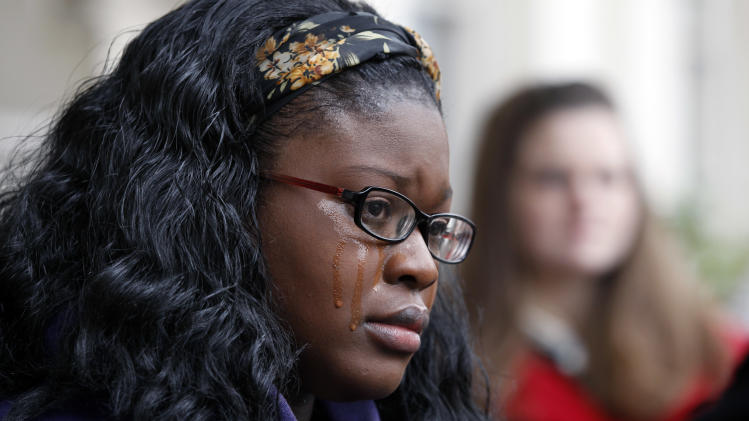 Tyamba Lamie, 22, cries as she listens to her mother Ingrid Johnson speak to a large gathering outside the New Jersey Statehouse in Trenton, N.J. on Friday, Jan. 11, 2013. Tyamba Lamie, who had run away from home, was forced into prostitution shortly afterwards at the age of 13. Johnson and others want to raise awareness of human trafficking. States around the country are passing laws to vacate the criminal convictions of people found to have engaged in illegal activity as victims of human trafficking. At least seven states have passed such laws. Others, including New Jersey, are considering similar legislation. (AP Photo/Mel Evans)
